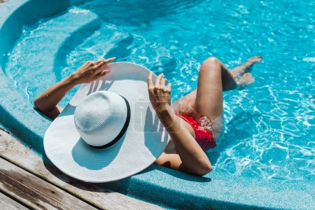 young woman touching straw hat and sitting in red swimsuit near swimming pool