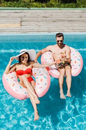 Photo pour Vue aérienne de la femme en chapeau de paille et bel homme tenant des verres à cocktail - image libre de droit