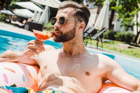 hombre barbudo guapo en gafas de sol sosteniendo copa de cóctel