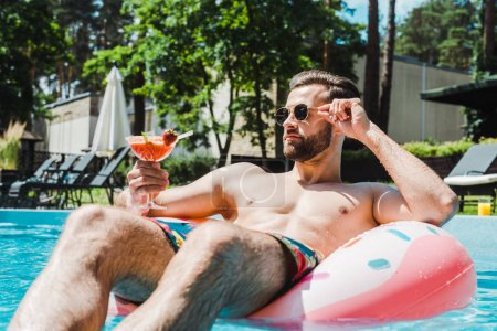 Photo for Selective focus of man touching sunglasses and holding cocktail glass - Royalty Free Image