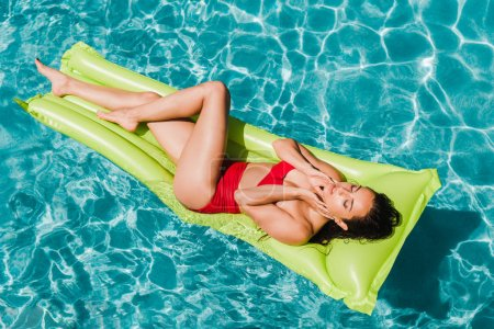 Photo for Overhead view of sexy girl with closed eyes lying on green inflatable mattress in swimming pool - Royalty Free Image