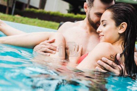 Photo pour Foyer sélectif de l'homme barbu beau et de la jeune femme souriant dans la piscine - image libre de droit