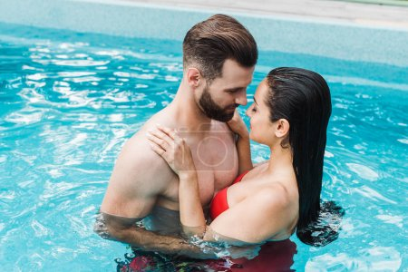 Photo for Brunette woman with closed eyes hugging handsome bearded man in swimming pool - Royalty Free Image