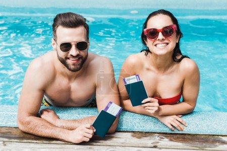 Photo pour Homme et femme gai dans des lunettes de soleil retenant des passeports avec des billets d'avion - image libre de droit