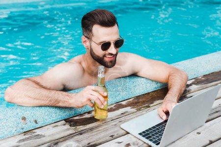 Photo pour Homme barbu gai dans des lunettes de soleil utilisant l'ordinateur portatif tout en retenant la bouteille avec la bière - image libre de droit
