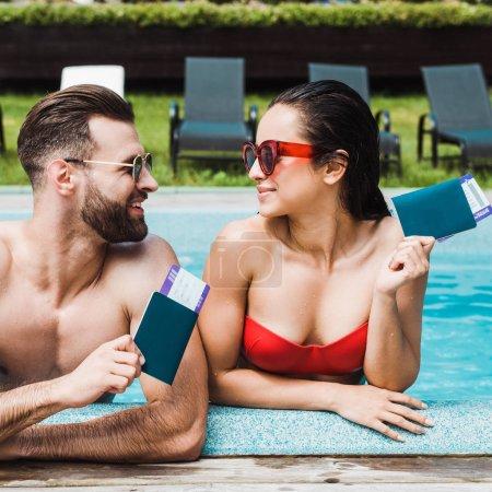 Photo pour Femme et homme heureux dans des lunettes de soleil retenant des passeports avec des billets d'avion - image libre de droit