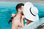 selective focus of muscular man and young woman in straw hat covering faces