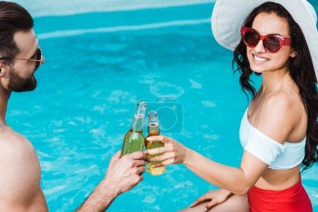 Photo pour Femme heureuse en chapeau de paille et bel homme cliquetis bouteilles avec de la bière - image libre de droit