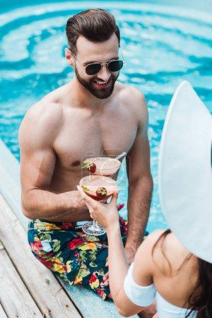Photo pour Foyer sélectif de heureux homme cliquetis verres à cocktail avec femme en chapeau de paille - image libre de droit