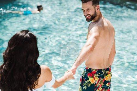 Photo pour Foyer sélectif de l'homme et de la femme heureux retenant des mains près de la piscine - image libre de droit