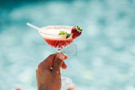 Photo pour Vue recadrée de l'homme tenant verre à cocktail avec boisson alcoolisée - image libre de droit