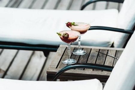 Foto de Enfoque selectivo de copas de cóctel con bebidas en la mesa de madera cerca de tumbonas - Imagen libre de derechos