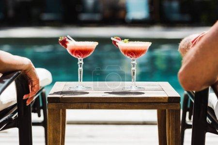Photo pour Vue recadrée de l'homme et de la femme sur des chaises longues près de la table avec des cocktails - image libre de droit