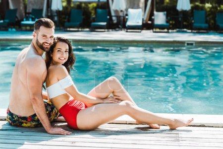 Photo pour Homme barbu heureux s'asseyant avec la femme attirante sur des plate-formes en bois près de la piscine - image libre de droit