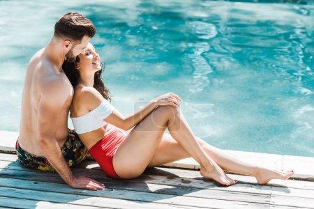 Photo pour Homme heureux s'asseyant avec la femme attirante sur des plate-formes en bois près de la piscine - image libre de droit