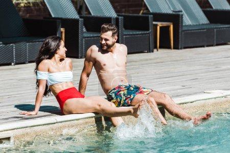 Photo pour Homme heureux regardant femme tout en étant assis sur des terrasses en bois près de la piscine - image libre de droit