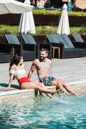 Photo pour Homme joyeux regardant femme tout en étant assis sur des terrasses en bois près de la piscine - image libre de droit