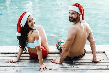 Photo pour Homme et femme joyeux chapeaux santa claus assis sur des terrasses en bois près de la piscine - image libre de droit
