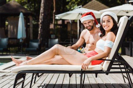Photo pour Homme et femme joyeux chapeaux santa claus assis sur des chaises longues en bois - image libre de droit