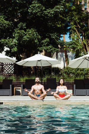 Photo for Attractive woman and handsome man meditating near swimming pool - Royalty Free Image