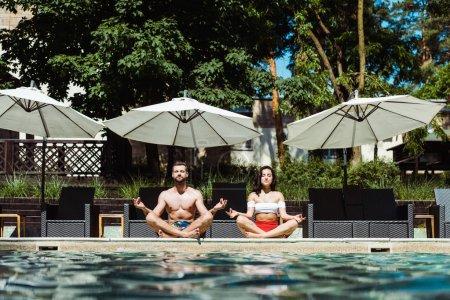 Foto de Hermosa mujer y hombre guapo meditando cerca de la piscina - Imagen libre de derechos