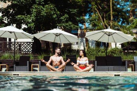 Photo pour Foyer sélectif de femme heureuse et bel homme méditant près de la piscine - image libre de droit