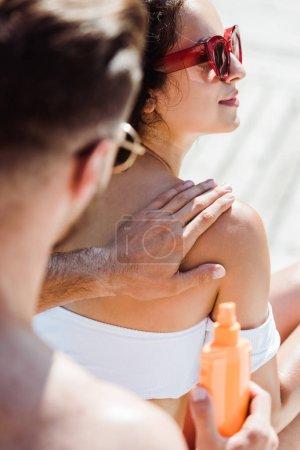 Photo pour Vue recadrée de femme touchantd d'homme dans des lunettes de soleil et en retenant la bouteille avec le sunblock - image libre de droit
