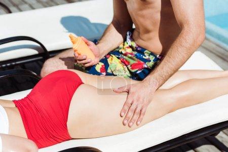 Photo pour Vue recadrée de l'homme touchant jeune femme couchée sur la chaise longue et tenant bouteille avec crème solaire - image libre de droit