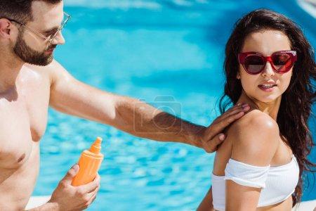 Foto de Hombre guapo tocando a la joven mujer en gafas de sol y sosteniendo la botella con bloqueador solar - Imagen libre de derechos