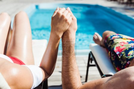Photo for Cropped view of man and young woman holding hands near swimming pool - Royalty Free Image