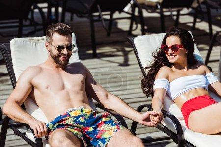 Photo pour Heureux homme et femme dans des lunettes de soleil tenant la main tout en étant couché sur des chaises longues - image libre de droit