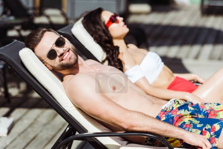 Photo for Selective focus of happy muscular man in sunglasses lying on deck chair near woman - Royalty Free Image