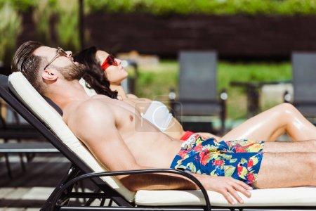 Photo pour Foyer sélectif de l'homme musclé dans les lunettes de soleil couché sur la chaise longue près de la femme - image libre de droit