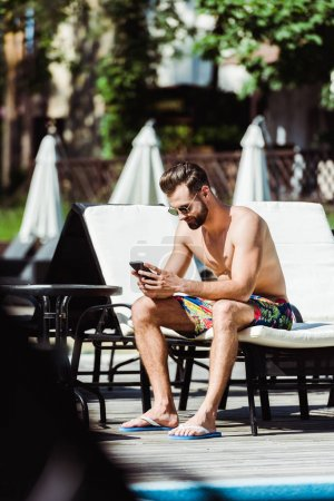 Photo for Selective focus of handsome bearded man sitting on deck chair and using smartphone - Royalty Free Image