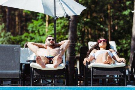 Photo pour Homme beau et belle femme dans des lunettes de soleil se trouvant sur des chaises de plate-forme - image libre de droit