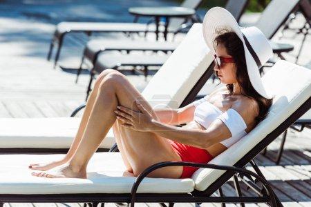 Photo pour Attrayant et élégant femme en paille chapeau et lunettes de soleil assis sur chaise longue - image libre de droit
