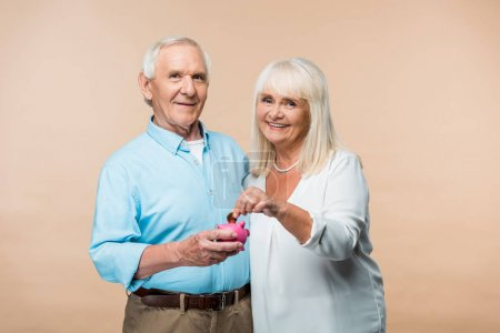 Photo pour Homme retraité gai retenant la tirelire rose tandis que la femme aînée mettant la pièce d'monnaie d'isolement sur le beige - image libre de droit