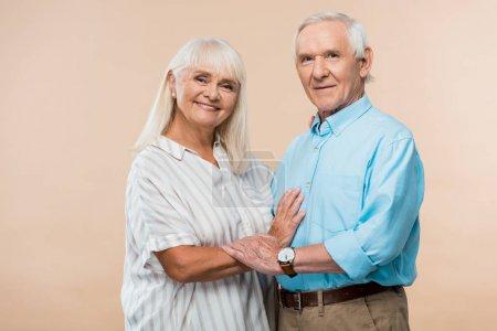 Photo pour Couples aînés gais souriant tout en restant sur le beige - image libre de droit