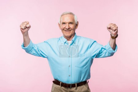 Photo for Cheerful retired man showing fists and smiling on pink - Royalty Free Image