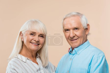 Photo for Happy retired couple with grey hair looking at camera isolated on beige - Royalty Free Image