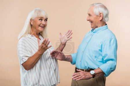 Photo for Happy senior wife gesturing while looking at husband isolated on beige - Royalty Free Image