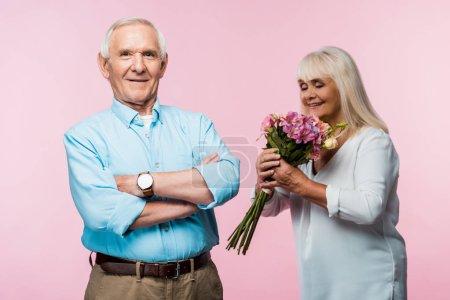 Photo pour Foyer sélectif de l'homme aîné heureux avec les bras croisés près de la femme heureuse avec des fleurs sur le rose - image libre de droit
