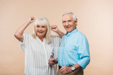 Photo for Cheerful senior woman gesturing near happy husband on beige - Royalty Free Image