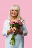 "Постер, картина, фотообои ""happy senior woman standing with bouquet of blooming flowers isolated on pink """