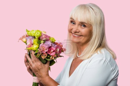 Photo for Happy senior woman holding blooming flowers isolated on pink - Royalty Free Image