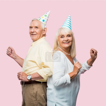 Photo for Positive senior husband and wife in party caps gesturing isolated on pink - Royalty Free Image