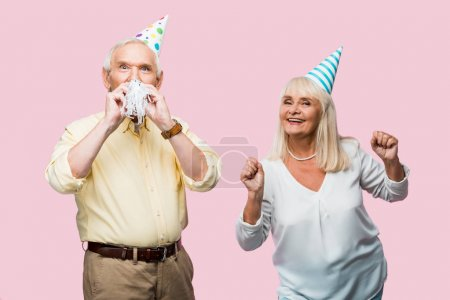 Photo pour Homme aîné couvrant le visage avec le souffleur de partie près de la femme gaie dans le chapeau de partie gturing isolé sur le rose - image libre de droit