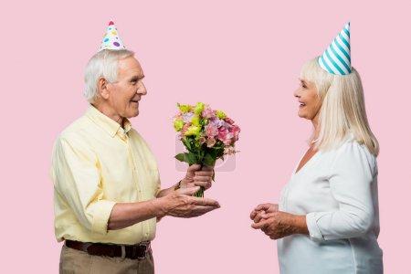 Senior-Mann überreicht Blumenstrauß an glückliche Frau in Partymütze