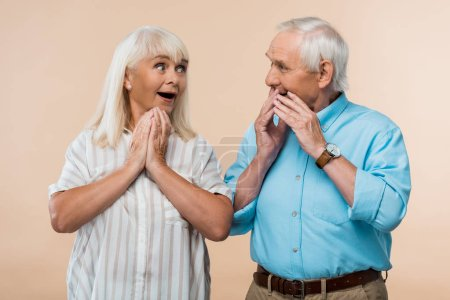 Photo for Surprised senior woman looking at husband covering face with hands isolated on beige - Royalty Free Image