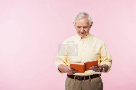 Photo pour Livre de lecture heureux d'homme retraité et souriant sur le rose - image libre de droit